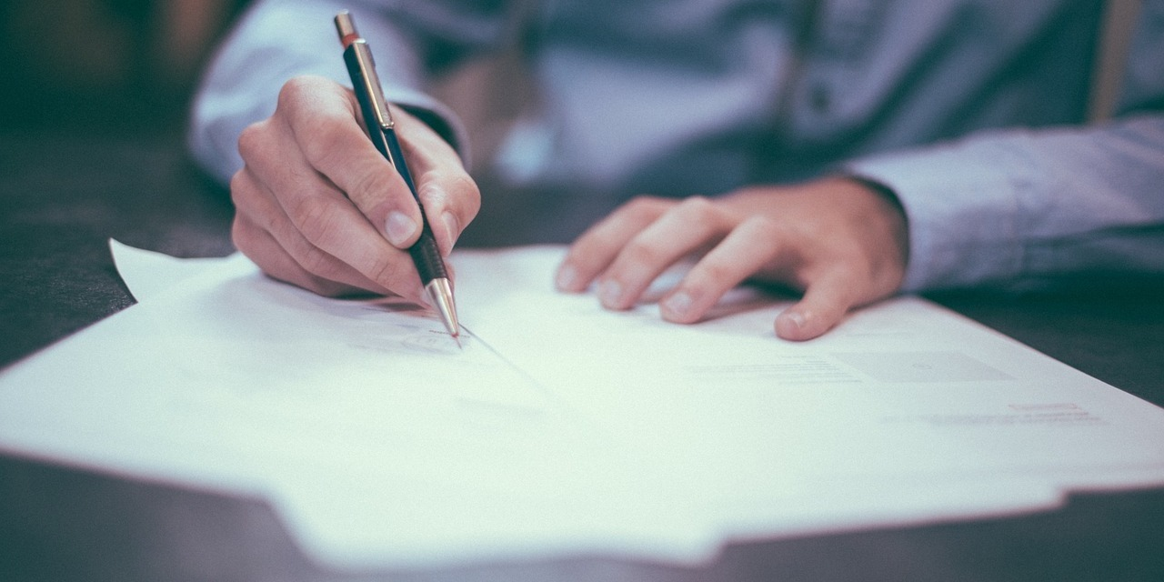 man-signing-documents