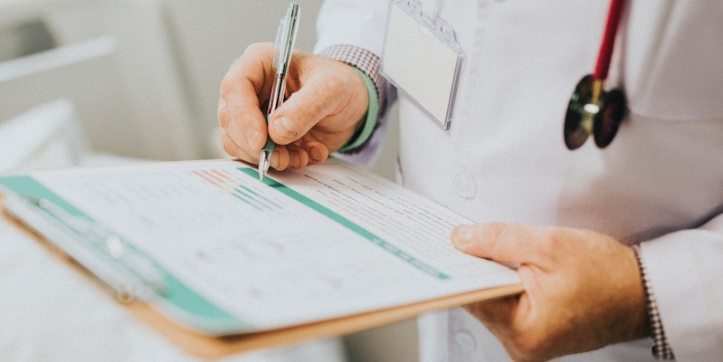 doctor-making-notes-on-clipboard