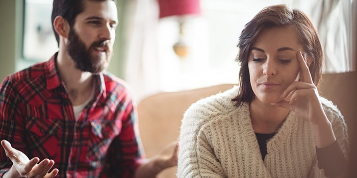 couple-arguing-on-sofa-woman-with-head-in-hands-divorce